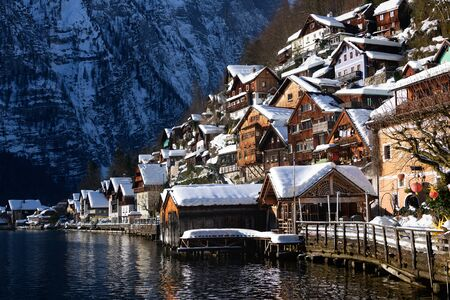 The traditional wooden lakeside houses of Hallstatt town with snow on the roofs in the first sunlight of the morning and with Alps mountains in the background in winter in Gmunden, Upper Austria.