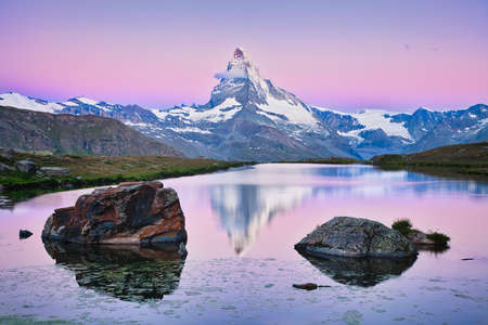 The summit of Matterhorn mountain with some snow at sunrise with reflection in the still water of Stellisee lake with big rocks in the foreground at 2537 m elevation, high above Zermatt on a cold morning in the Alps in Switzerland. Imagens