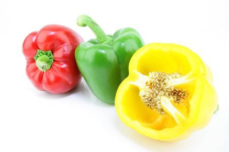 A row of fresh green, red and a cut yellow paprika  Capsicum annuum  on a white background  Stock Photo - 15437017