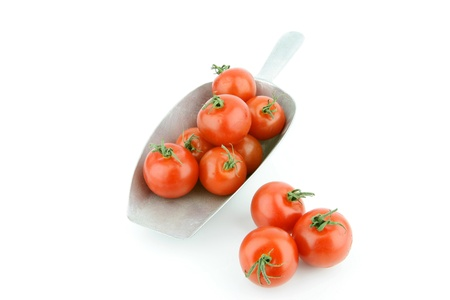 lycopene: Fresh ripe tomatoes in a aluminum grocery scoop on a white background
