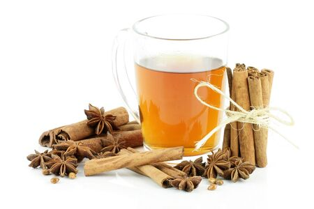 cinammon: A glass of tea with cinnamon and star anise, on a white background