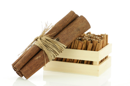 cannelle: Three cinnamon sticks wrapped together and a wooden crate.