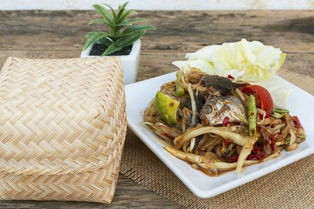 tam: Thailand papaya salad, sticky rice, bamboo and ceramic containers that are placed on an old wooden table.  SOM TAM  Stock Photo