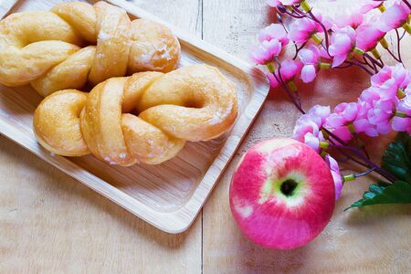 sugarcoated: Bread, sugar-coated, apple and flowers on a wooden table.
