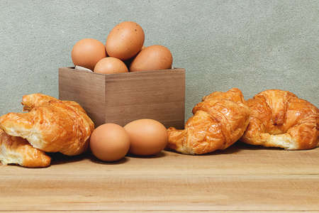 Croissant and eggs in a wooden box on a wooden table in the kitchen. Breakfast concept.