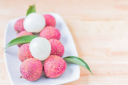 litchee: Fresh lychees in white ceramic dish on wooden table. Thailand litchi varieties Emperor