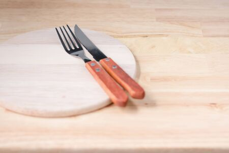 prong: Selective focus at prong of fork on chopping wood. Placed on wooden table. Kitchenware concepts.