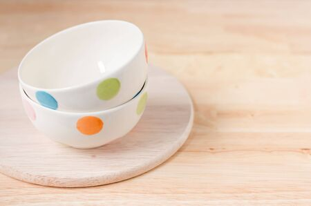 Selective focus at cup with orange dots on chopping wood. Placed on wooden table. Kitchenware concepts.