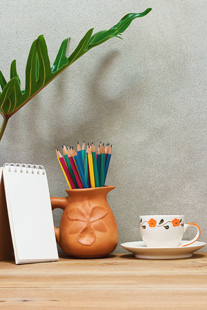 pencil plant: Pencil in earthenware vase, coffee cup and notebook on a wooden table under a foliage plant.