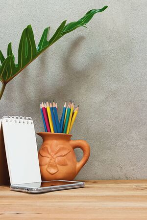 pencil plant: Pencil in earthenware vases, mobile phone and notebook on a wooden table under a foliage plant.
