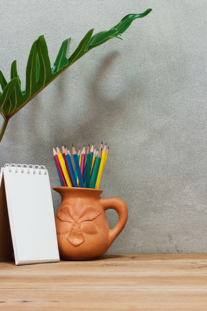 Pencil in earthenware vases and notebook on a wooden table under a foliage plant.