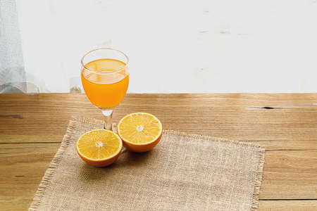 Warm breakfast, orange juice on table beside windows