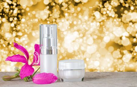 care about the health: Cosmetics bottles and Orchid Tree Chongkho flowers on wooden table blur and bokeh golden white background. For use as product offering, packaging design to sample bottles and jar cream. Who care about their health and beauty.