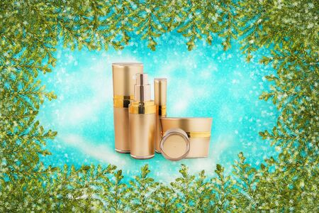 Golden cosmetic cans of moisturizer and Pine branches on winter background of blue sky with snow.