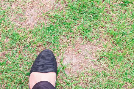 green been: Woman feet wearing black shoes stepping on the green grass that has not been taken care of.