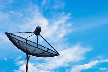 Black satellite dish or TV antennas on blue sky cloudy background.