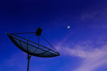 Black antenna communication satellite dish or TV antennas in evening blue dark sky cloudy with moon and stars for background.