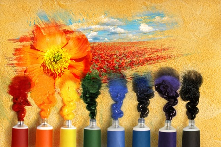 Tubes of paint and picturesque landscape with poppie  photo