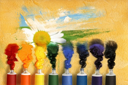 Tubes of paint and picturesque landscape with camomile photo
