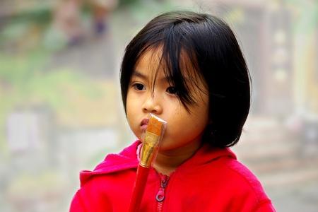 HOI AN, VIETNAM- JANUARY 17: Portrait of the vietnamese girl on a street in Hoi An. January 17, 2011 in Hoi An, Vietnam Stock Photo - 13574252