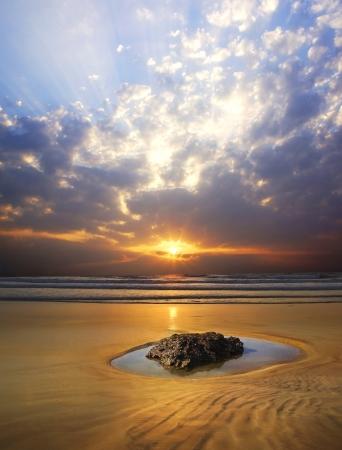 arena: Pintoresco paisaje marino con rocas en primer plano