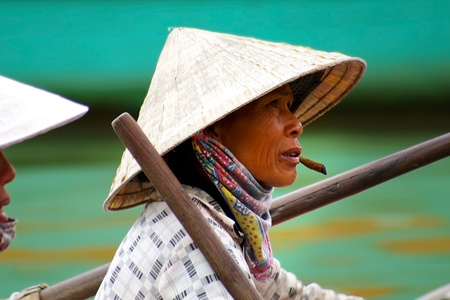 conical hat: HOI AN, VIETNAM- JANUARY 17: Portraits of the woman-ferryman on a street in Hoi An.