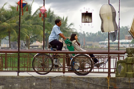 adult vietnam: HOI AN, VIETNAM- JANUARY 17 2011: Cyclo driver and passenger in Hoi An. Editorial