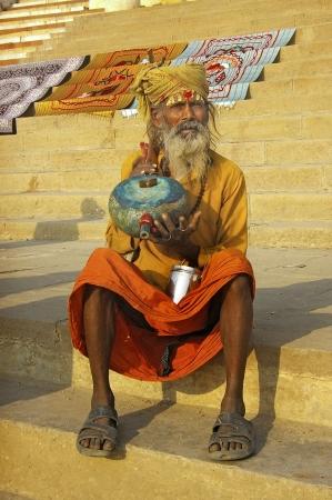 VARANASI, INDIA - FEBRUARY 27: A sadhu relaxing on the bank of river Ganga on Febuary 27, 2006 in Varanasi, India. In Hinduism, sadhu (good man, holy man) denotes an ascetic, wandering monk.  Stock Photo - 19235511