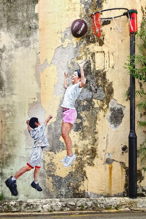 GEORGETOWN, MALAYSIA - JANUARY 19, 2014  Street Art by artist Louis Gan  Children Playing Ball   It graces the wall of the Kwong Wah Yit Poh warehouse along Chulia Street Ghaut