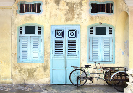 Riksja op de achtergrond van een traditioneel huis. Stockfoto
