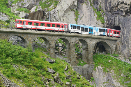 ancient pass: Devils bridge with train at St. Gotthard pass. Switzerland Editorial