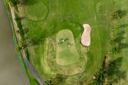 Aerial top view photo from flying drone of Golf Course, Lush green grass on golf course with path for golf cart, Group playing golf and flag Archivio Fotografico