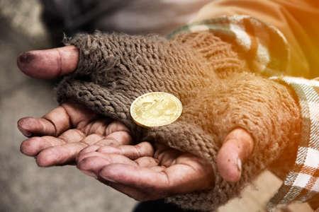 Beautiful hand homeless man holding gold bitcoin close up.