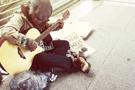 Beautiful Homeless man playing guitar on walking street in the capoital city.