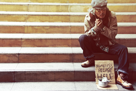 Could you please help homeless man on walkway street in the capticap city. Stock Photo
