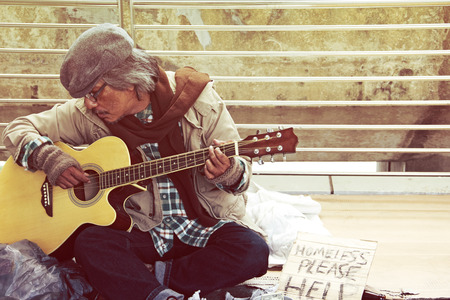 Beautiful Homeless man playing guitar on street in the capital city. Stock Photo