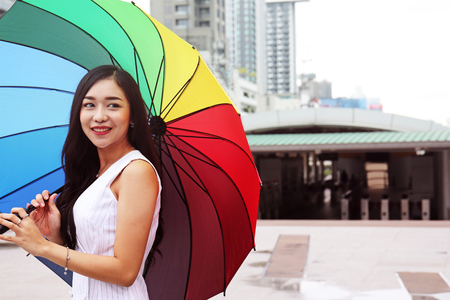 Beautiful women holding umbrella on the walking street city. Imagens