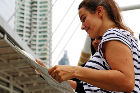Young women are introducing tourist attractions to tourists on paper map.
