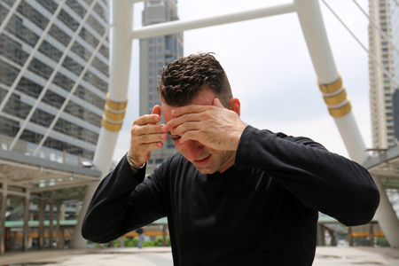 Sport man exercise Outdoor fitness hot and tired on walking street, Building office background.