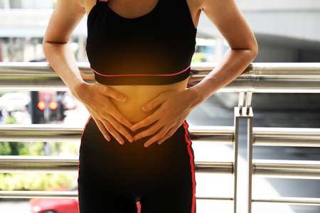 Female athletes, abdominal pain, menstrual period during exercise on walking street in the city.