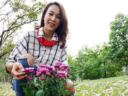 Beautiful woman holding flowers for planting in the public park.
