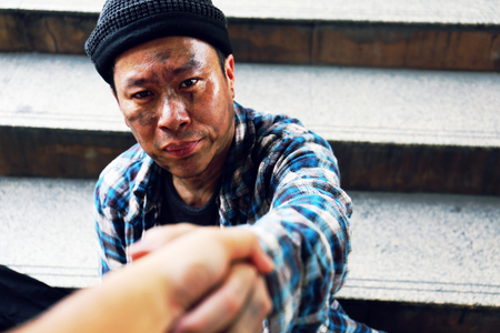 Close-up handshake for help homeless man on walking street in the capital city. Stock Photo