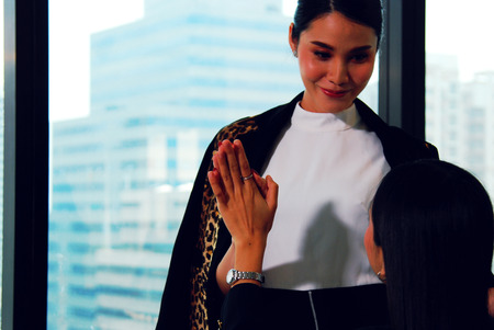 Beautiful Business woman greeting girl friend in office and office building background. 版權商用圖片