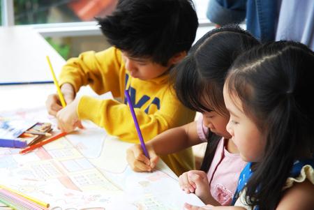 Les enseignants enseignent le dessin sur du papier blanc à trois enfants pendant le week-end de vacances. Flou d'arrière-plan