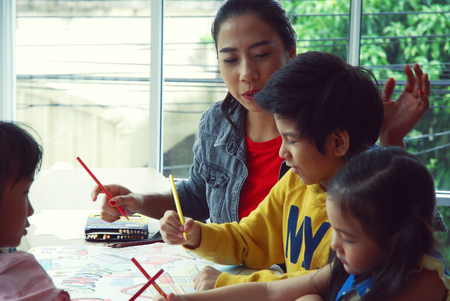 Teachers are teaching drawing on white paper to three children in holiday weekend. Background blur Stockfoto
