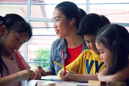 Niños niño y niñas aprendiendo a dibujar sobre papel blanco en fin de semana festivo.