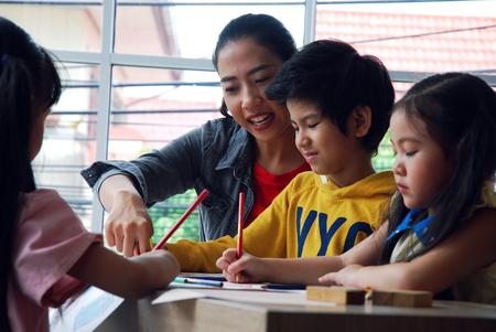 Niños niño y niñas aprendiendo a dibujar sobre papel blanco en fin de semana festivo. Foto de archivo