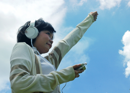 Beautiful girl listening music on headphone and retouch mobile phone device. Stockfoto