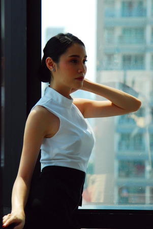 Beautiful Asia Business woman manager smile portrait and office building background in the capital city. 版權商用圖片
