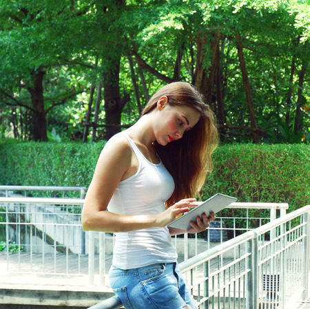 The young woman playing smart phone in public park.